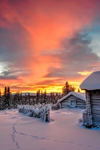 barn in the snow with a beautiful sunset