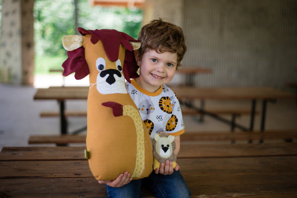 boy holding 2 lion stuffed animals