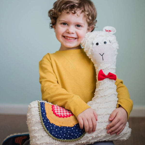 boy smiling with llama stuffed animal