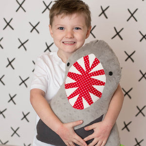 Boy holding shark stuffed animal