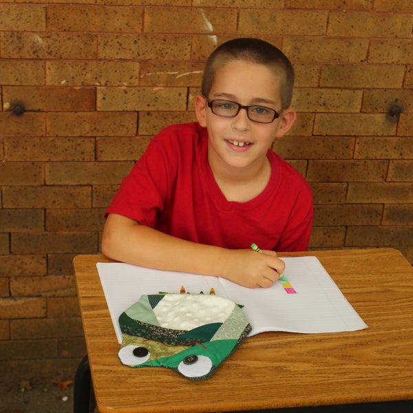 boy at desk with frog pencil case
