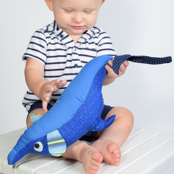 baby with stuffed animal dolphin