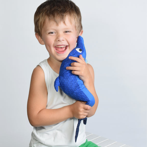 boy hugging dolphin stuffed animal