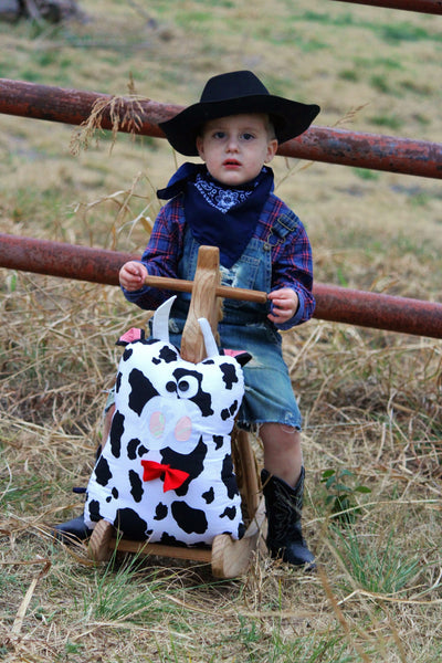 Boy on rocking horse with his cow  stuffed animal