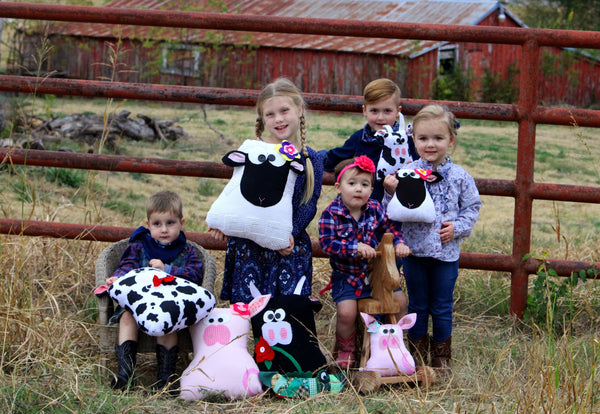 Group of kids on a farm with stuffed animals