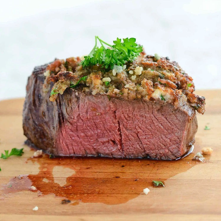 Bison Filet Mignon with sautéed garlic  on top garnished with a piece of parsley, sitting on a wood cutting board and cut showing a perfect Medium temperature with a little juice that has leaked out