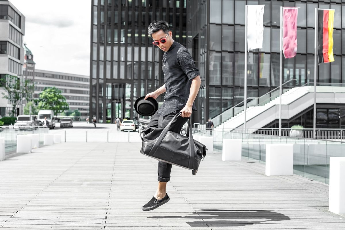 Man jumping and holding black luxury Sports Bags by Siebenhaar