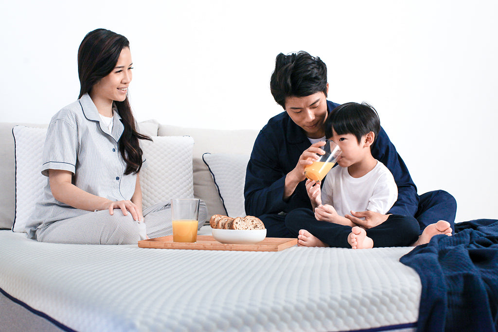A young boy's father helping him drink a glass of orange juice, next to his mother and a wooden tray of food, all on top of a Sonno Original mattress