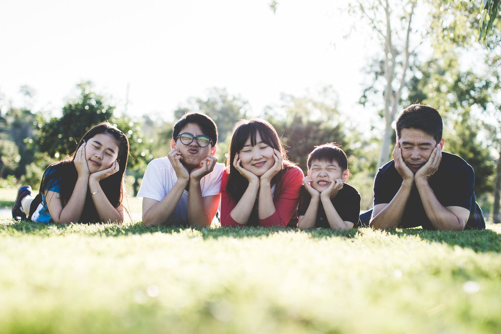 A family of five lying on the grass smiling at the camera, with their faces in their hands