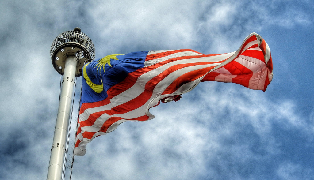 A Malaysian flag, or Jalur Gemilang, flying in the wind against a blue sky