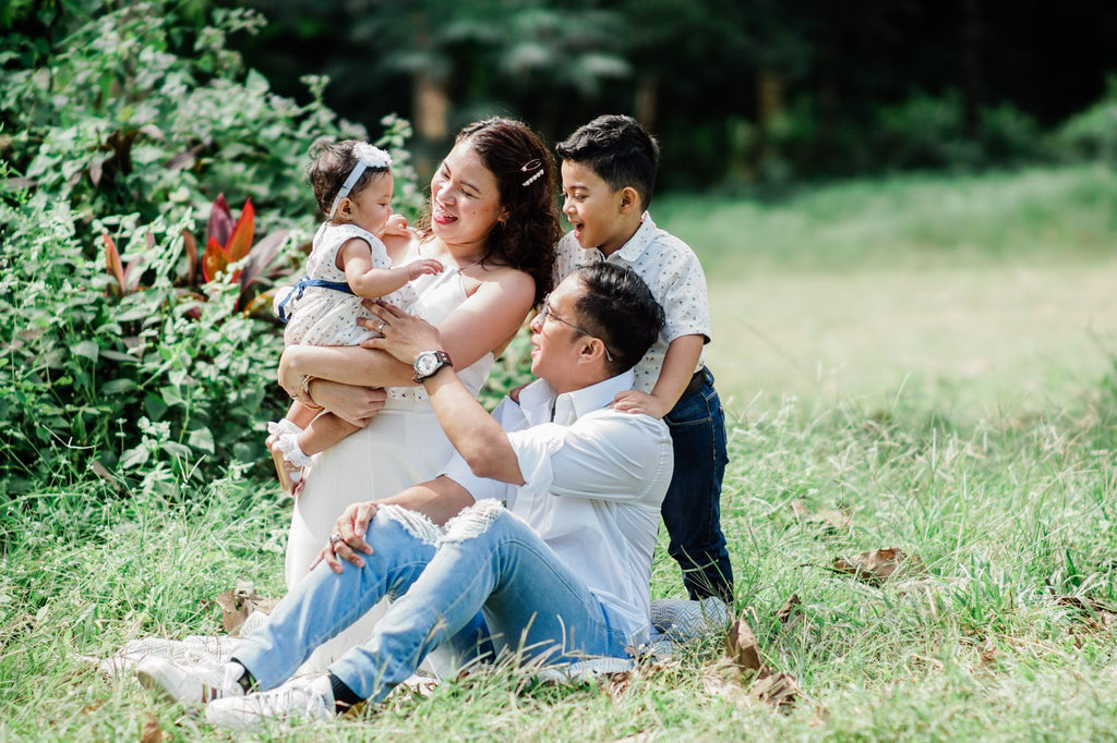 A family of four in the grass enjoying time together in the park