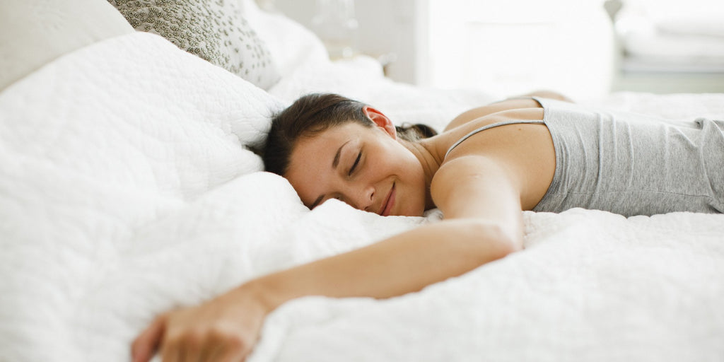 A woman sleeping on her stomach, with her hands underneath her pillow.