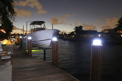 A boat docked on water in front of portable solar lights on the dock