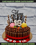 A chocolate loaded with cake with all kinds of chocolate and macaroons with a beautiful plastic birthday topper on top
