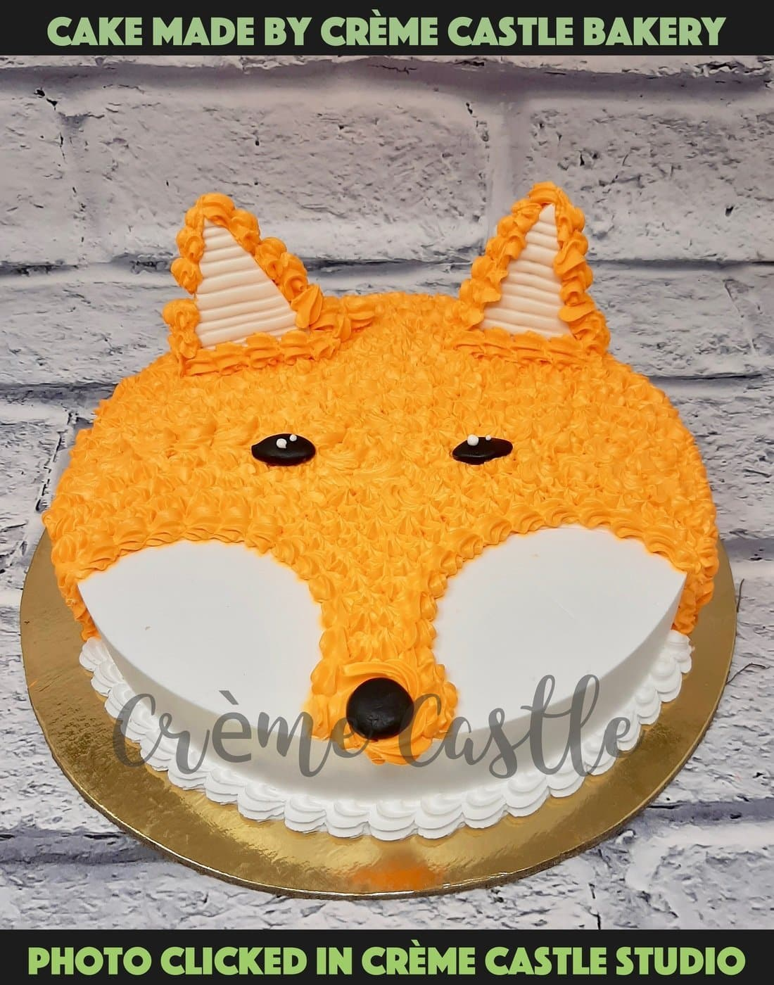 A cake in the form of the face of a dog in orange colour made from the cream and fondant made ears