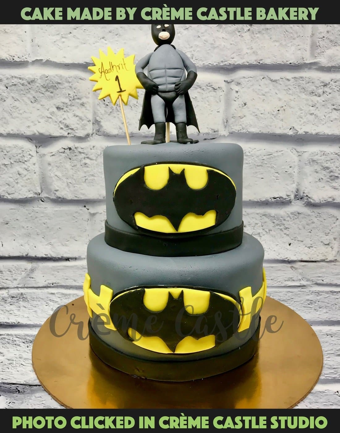 A fondant covered two tier cake in the theme of formidable Batman with logo on the edge and a handcrafted figure of Batman at the top