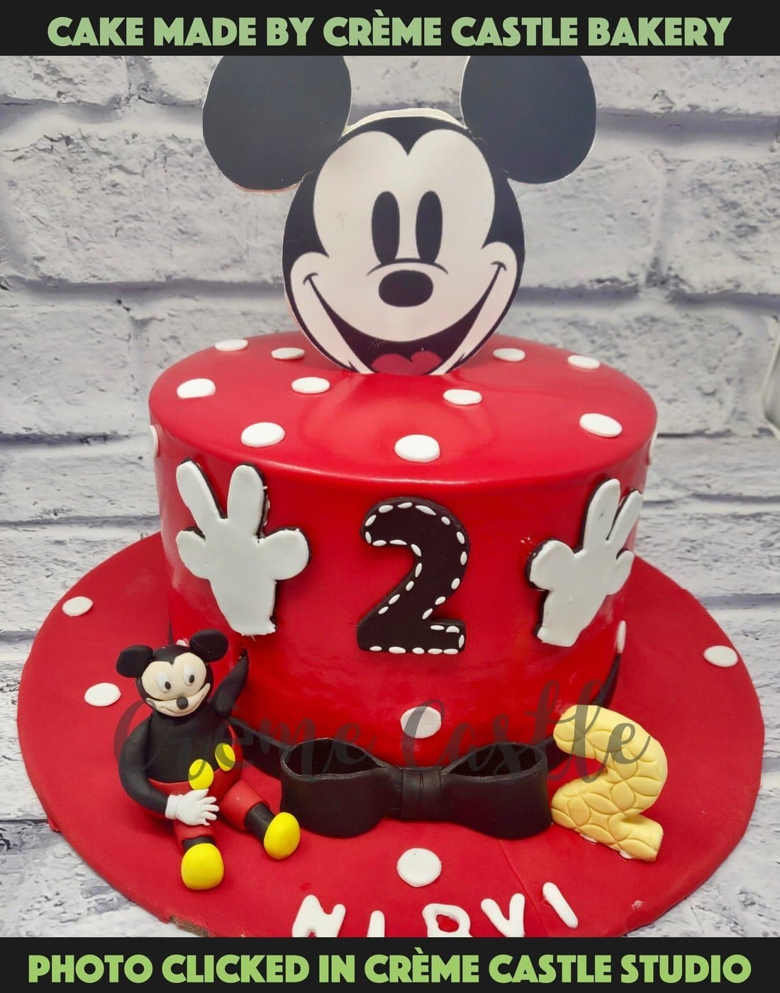 A typical Mickey Mouse theme cake with in red colour with Mickey face on top and hand crafted mickey mouse chilling at the bottom of the cake