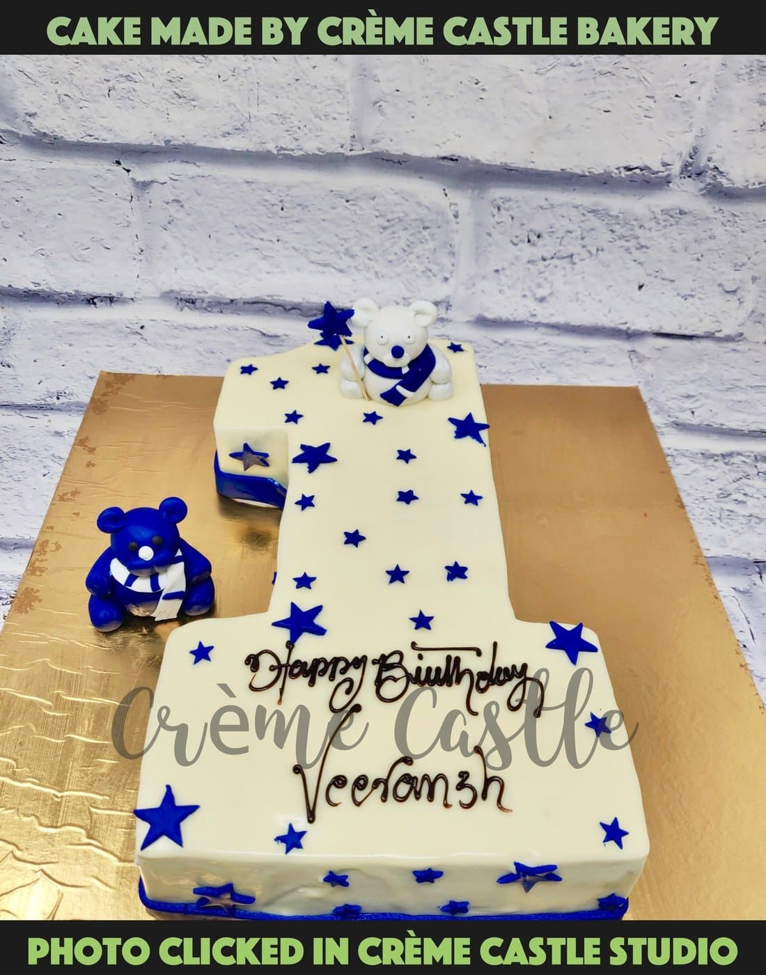 A cake for first birthday in the form of Number 1 in white theme with blue stars sprinkled all over the cake.