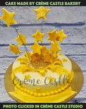 A white theme cake with golden stars all over the cake bursting out. A remarkable surprise.