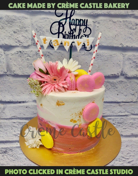 A buttercream made cake in colour tones white to pink with macaroons and real flowers sprinkled all over the cake.