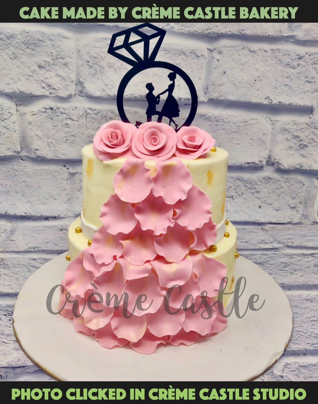 A tier cake in the form of a dress with roses on top and a topper of proposal. The flower petals flowing all over the cake giving it a dress like feel