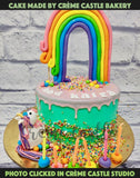 A cake with a grand rainbow at top of a drip cake with a cute unicorn at the bottom with a lot of fondant made candies. This cake is a real eye candy