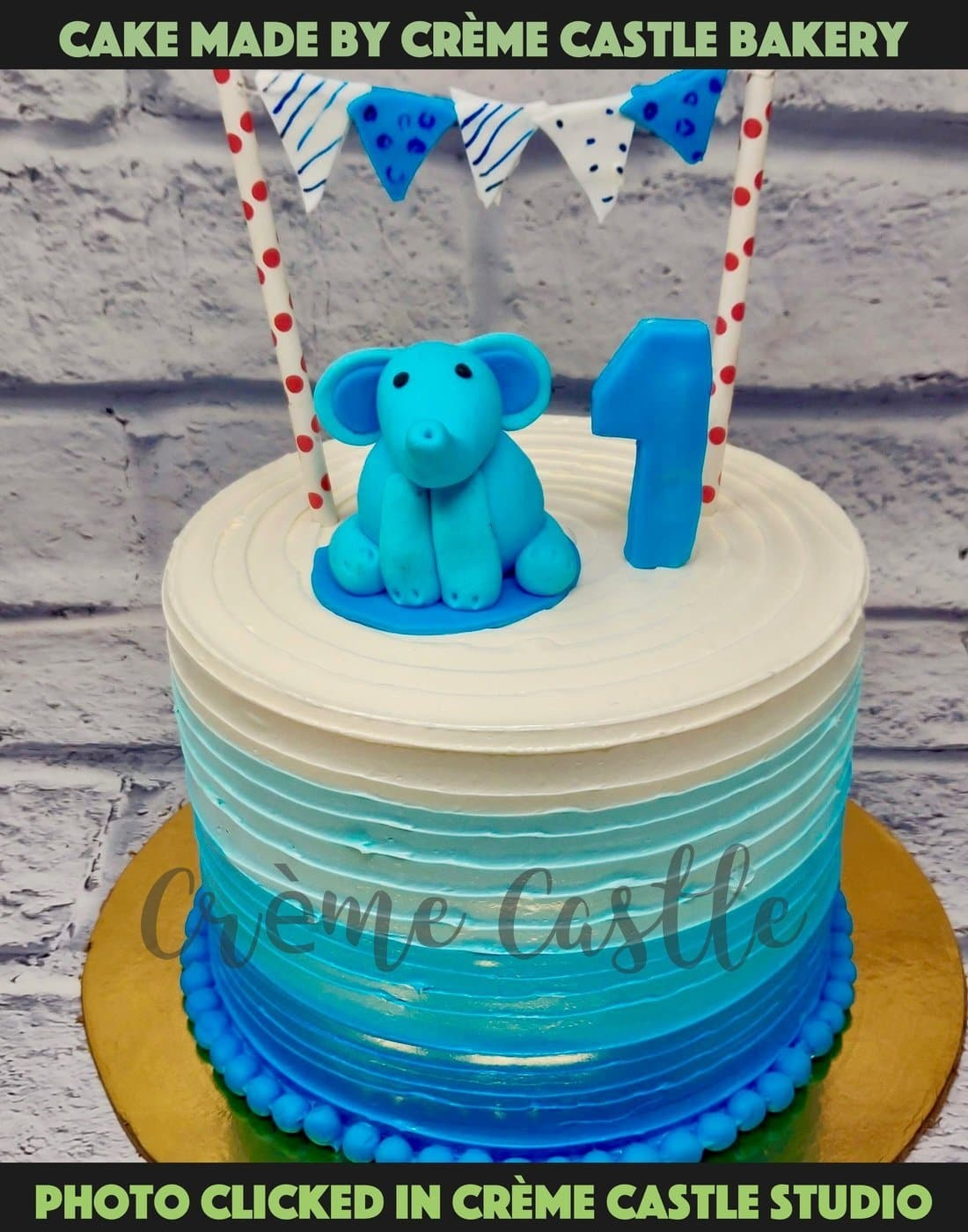 A cake for first birthday with blue to white colour tones on edges out of butter cream and baby elephant and number 1 on top