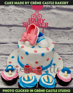 A cake for a baby shower with baby booties of red and blue colour are on top of cake