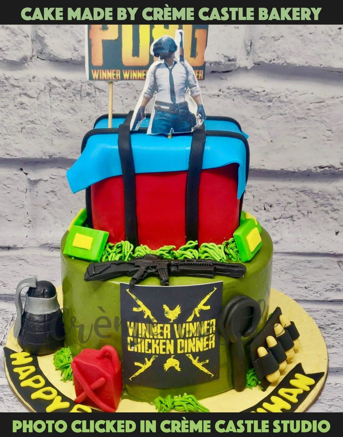 A one of a kind PubG 2 tier cake with a supply box on the top with main character on the top with guns, supplies, grenades and typical Winner Winner Chicken Dinner on top