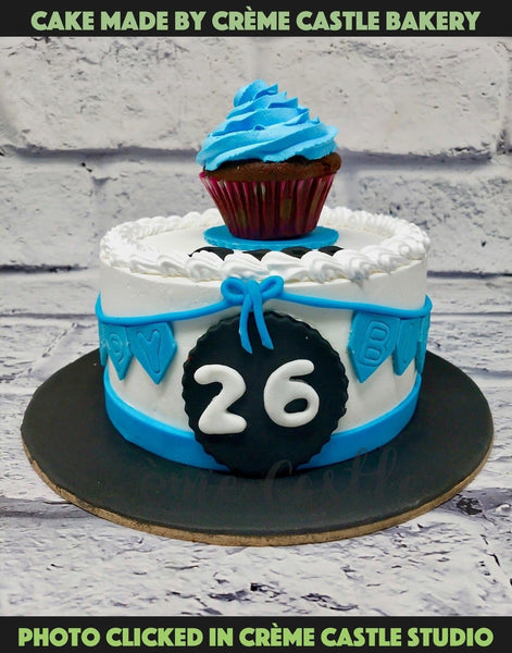 A cake with a cute cupcake on top made in blue and white theme.