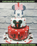 A red and white tier cake with mickey figure at the edge and Minnie face at the top with red and white polka dots all around the cake. A grand first birthday cake