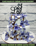 A cake made in fondant white lavender petal and branches and a beautiful topper on top