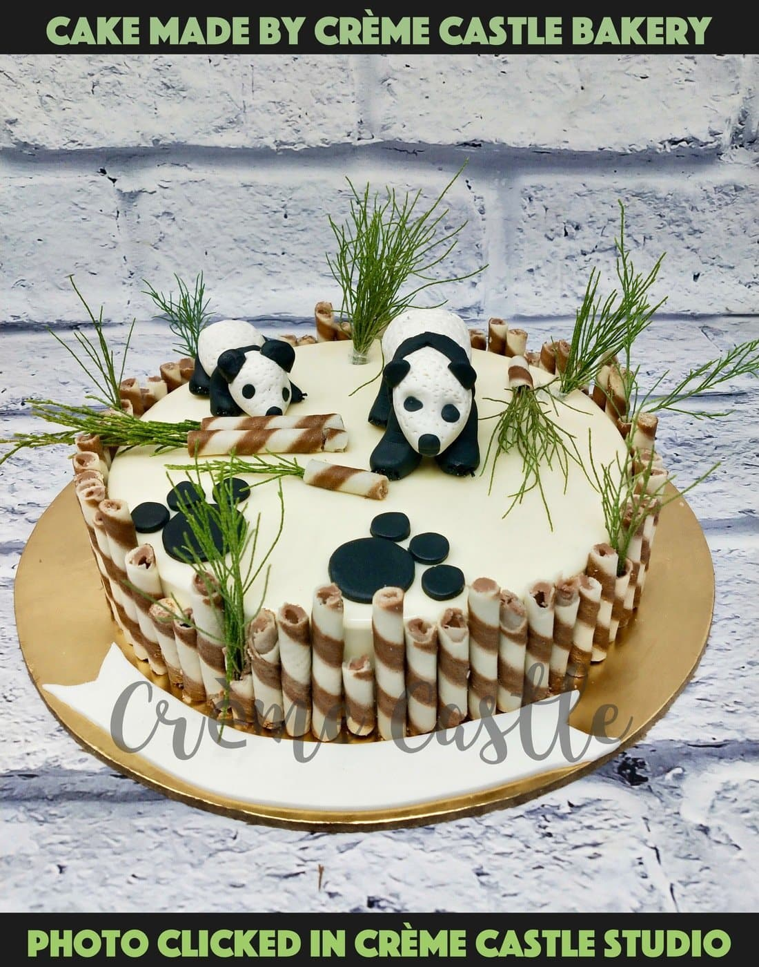 A white theme cake in a forest theme surrounded by chocolate cigars as boundary and bushes and pandas playing in between. How cute is that!