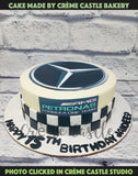A luxury car theme cake with Mercedes logo at the top and racetrack flags at the border of the cake.