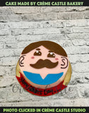 A cake with cute male face caricature on top.
