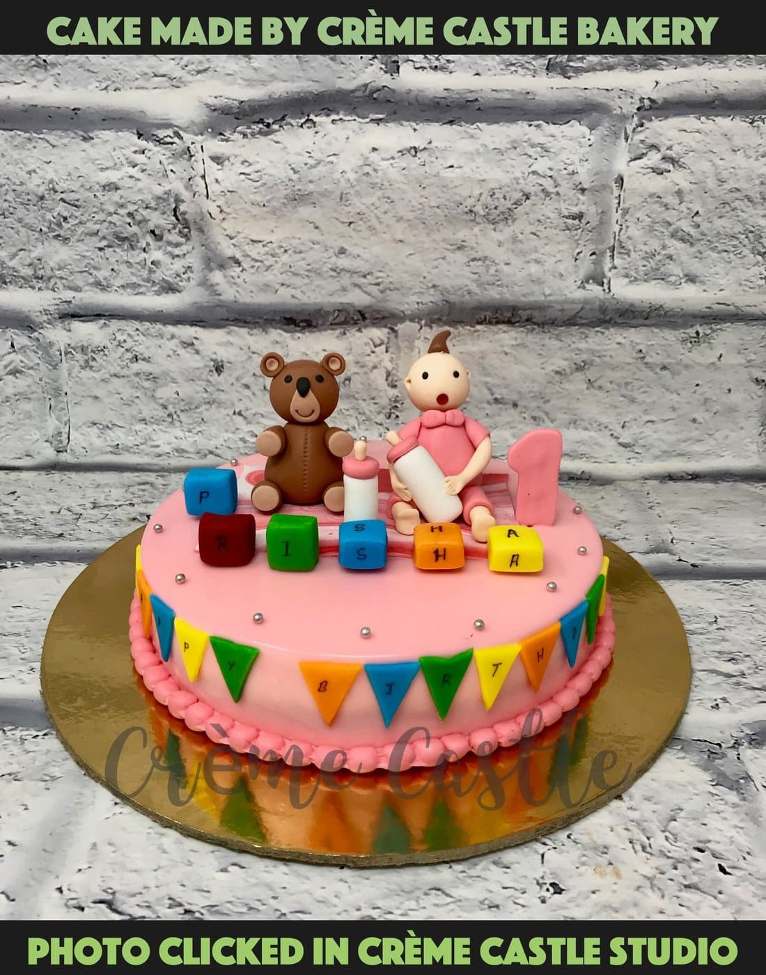 A cake for a baby girl with a cute teddy sitting besides her with all the toys around