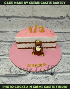 A 6 months birthday cake in pink theme for a baby girl with a cute teddy on top