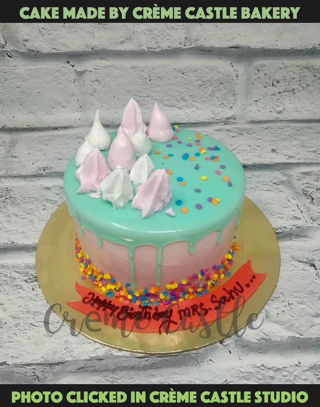A blue drip cake on pink base with pink meringues