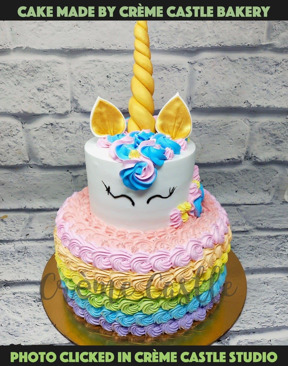 A tier cake in unicorn theme with rainbow in bottom tier made with cream swirl in multiple colors
