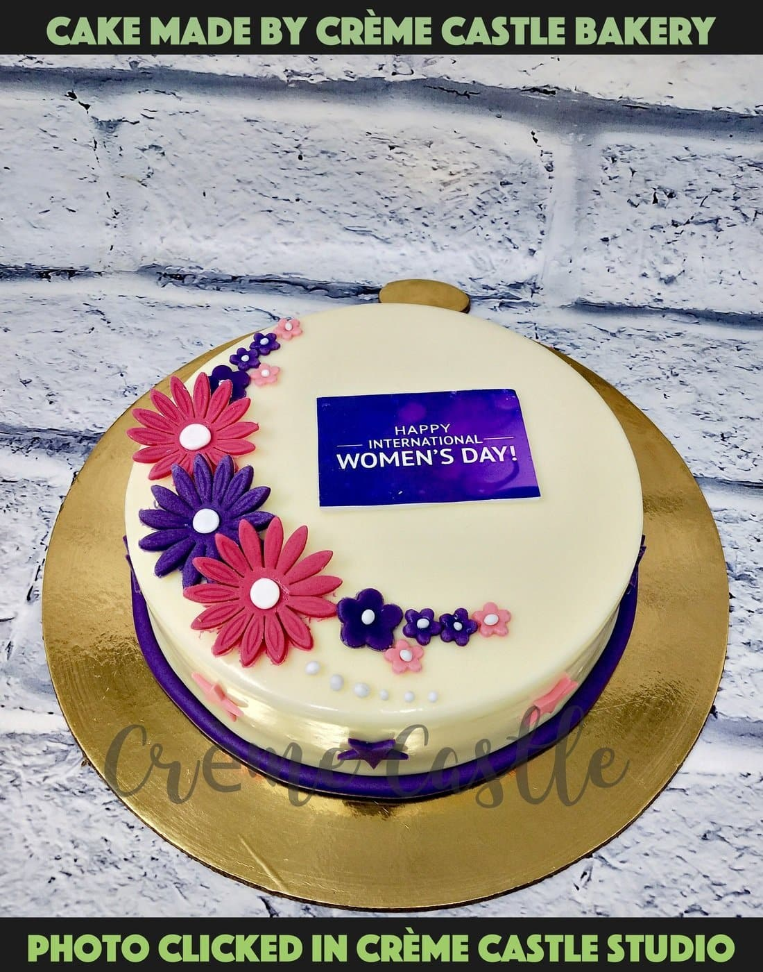 A cake for women's day in purple and pink theme with logo of women's day on top and similar colored flowers decorated all over cake