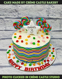 A white cream cake with candies on top and rainbow patter on the edge