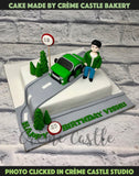 A cake for someone who has purchased a new car is totally in awe of it. A cake that shows someone chilling by the car on a road trip