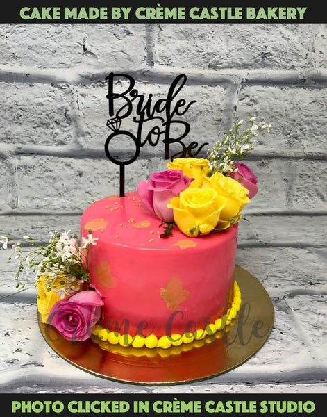 A pink color beautiful cake with real flowers decorated on cake for a to be bride.