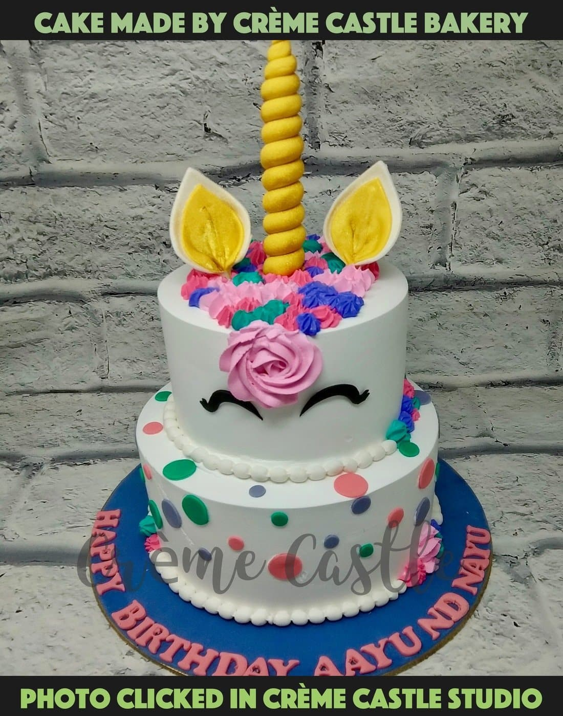 A cream based tier cake with unicorn theme on top and the bottom