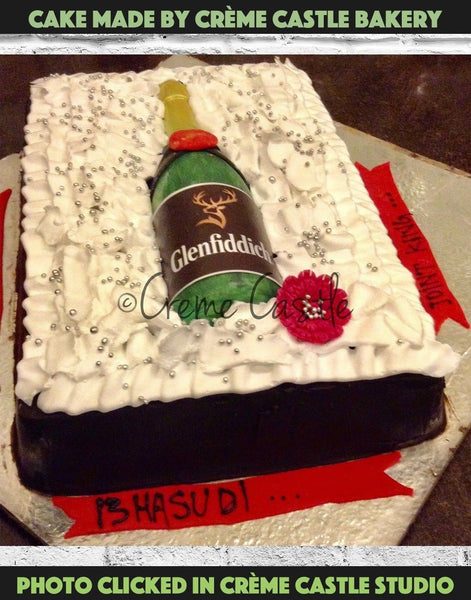 Whiskey theme cake for husband. A Whiskey gift pack shaped cake which has a malt whiskey bottle in the middle, looks like a real gift pack. Order cake online | Noida and Greater Noida