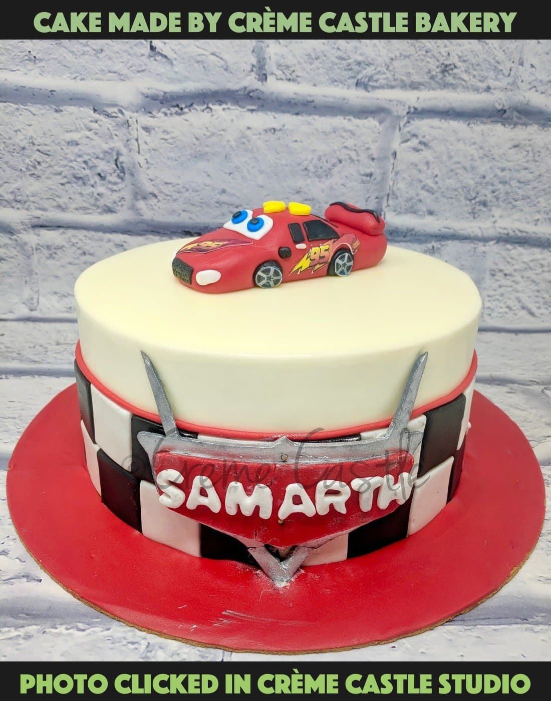 A cake based on Disney theme Cars on a race track on a Blue base with Lightning McQueen at the center of the cake