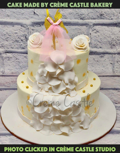 A Graceful Cake In All White With White Flowers On The Surface And A Pink Net Portraying A Wedding Gown Feeling With A Veil