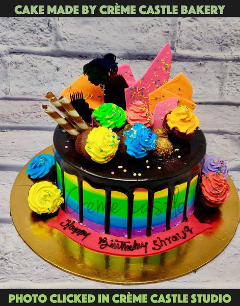 A Drip Cake With Chocolate Dripping On Top And Rainbow Shades On The Edge