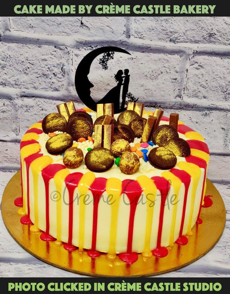 A Red And Golden Shades Drip Cake With Oreos, KitKat And Chocolate Chips On Top And Couple Topper
