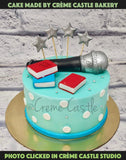 A blue theme cake with books and mic on top